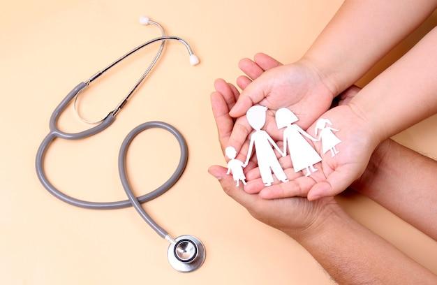 Hände halten papierfamilienausschnitt mit stethoskop.