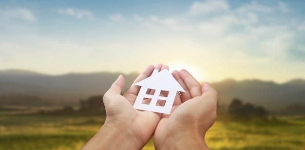 Hände halten papierhaus, familienhaus und schützendes versicherungskonzept