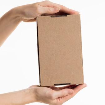 Hände halten pappkarton