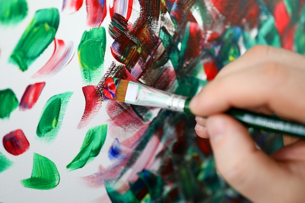 Hände halten pinsel mit mehrfarbiger farbe