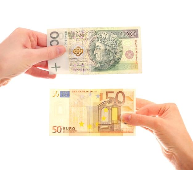 Hände halten polnischen hundert-zloty-schein und 50-euro-schein auf weißem hintergrund
