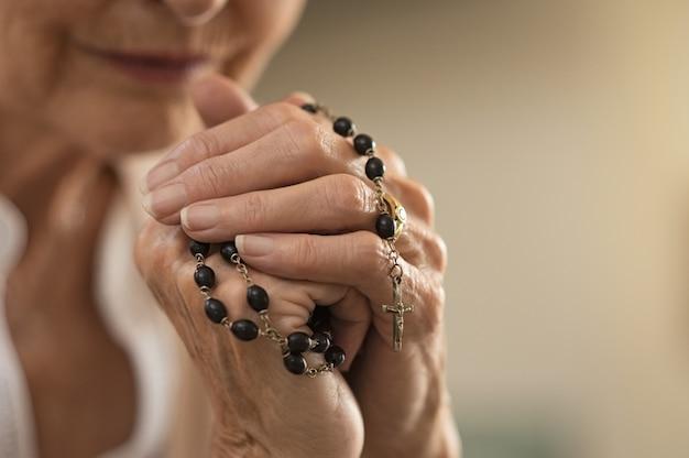 Hände halten rosenkranz und beten