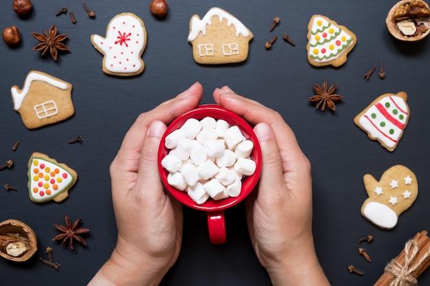 Hände halten rote keramikschale mit kakao und marshmallows auf hintergrund von weihnachtsplätzchen