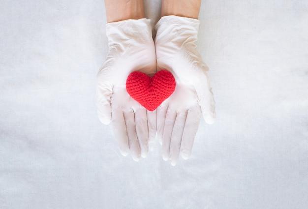 Hände halten rotes herz. herzgesundheit, kardiologie, arzttag, weltherztag. hypertonie.