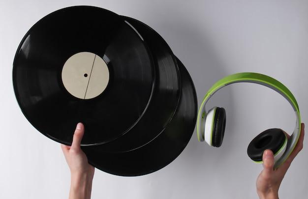 Hände halten schallplatten und kopfhörer auf einer weißen oberfläche