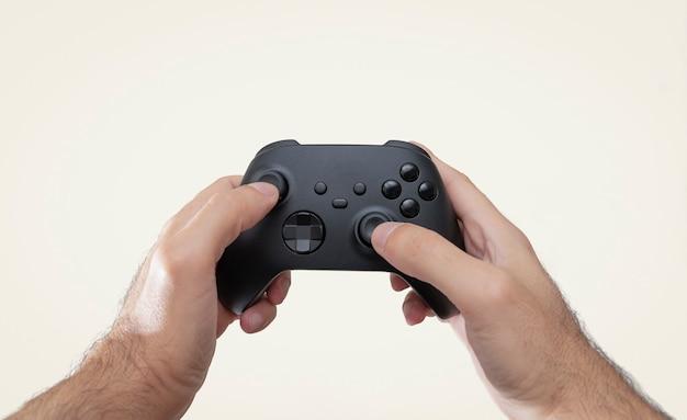 Hände halten schwarzen gamecontroller isoliert auf weißem hintergrund