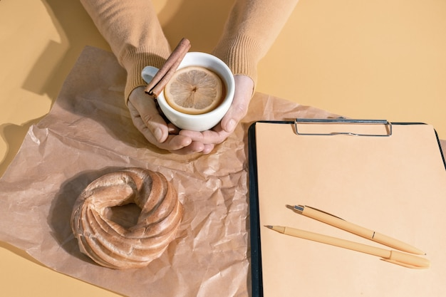 Hände halten tasse tee oder glühwein in der nähe von lebenslauf und kuchen