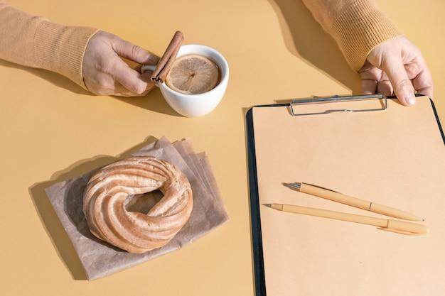 Hände halten tasse tee oder glühwein in der nähe von resume sheet und kuchen auf dem set segel champagner farbe hintergrund, draufsicht.