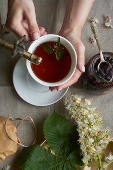 Hände halten tasse tee von vintage samowar und glas hausgemachte marmelade