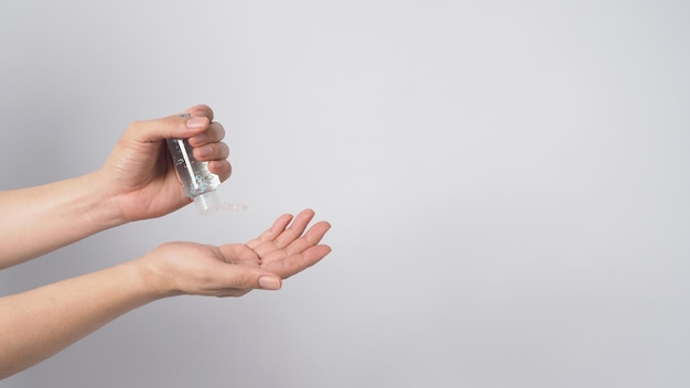 Hände halten und quetschen alkoholhandgel auf weißem hintergrund.