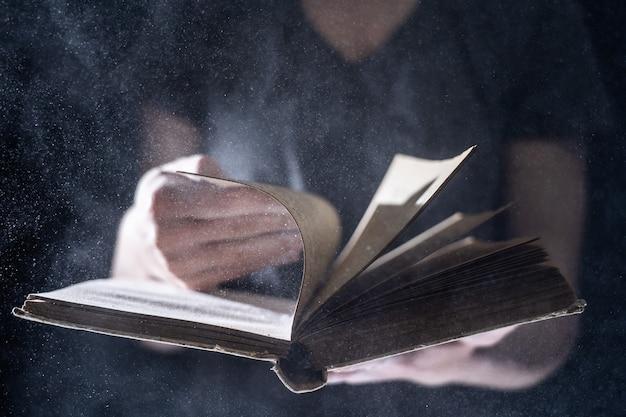 Hände halten vintage offenes buch leuchtet auf schwarzem hintergrund