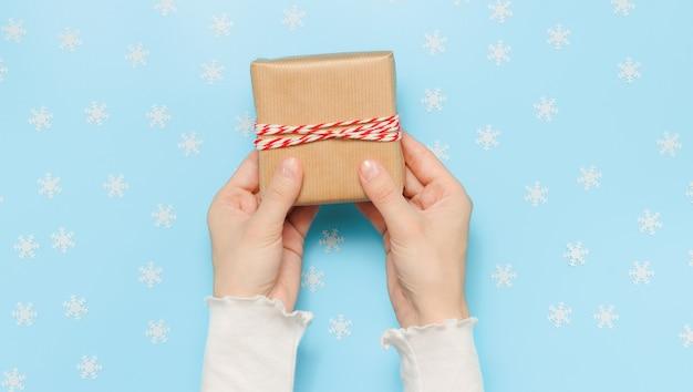 Hände halten weihnachtsgeschenkbox mit schneeflocken im hintergrund