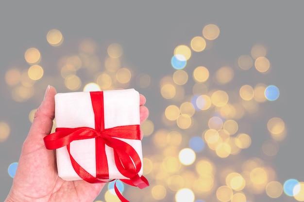 Hände halten weiße geschenkbox mit rotem band auf trendigem ultimate grey 2021 hintergrund