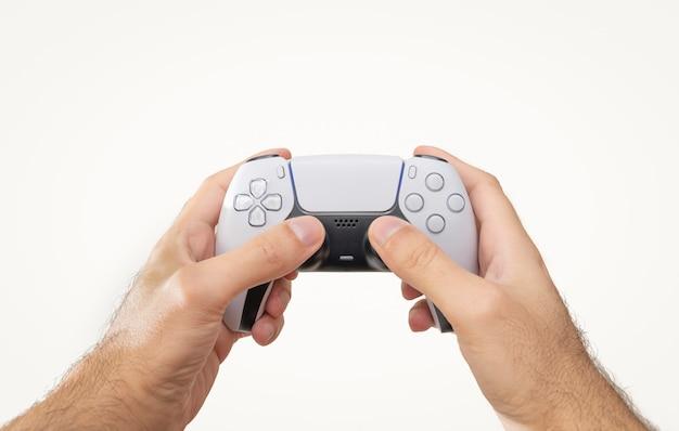 Hände halten weißen gamecontroller isoliert auf weißem hintergrund