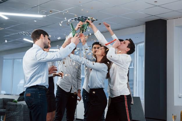 Hände hoch. foto des jungen teams in der klassischen kleidung, die erfolg feiert, während getränke im modernen gut beleuchteten büro halten