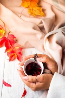 Hände hpld tasse tee mit herbstlaub auf holzoberfläche