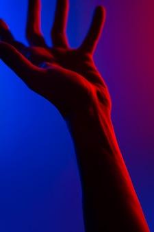 Hände im bunten kontrast-neonlicht des blauen rotes.