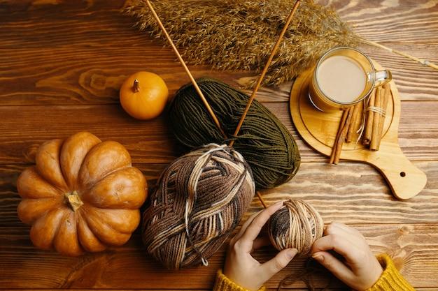 Hände im orangefarbenen pullover mit garnstricknadeln kaffee und zimtstangen auf holztischhandwerk...