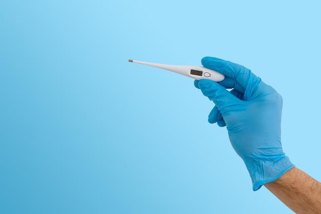 Hände in blauen handschuhen, die ein medizinisches thermometer halten