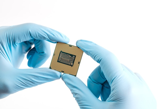 Hände in blauen handschuhen halten mikroprozessor-cpu auf weißem hintergrund nahaufnahme
