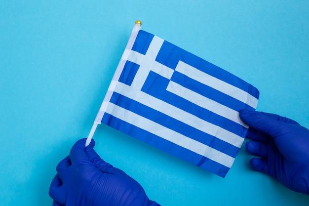 Hände in blauen latexhandschuhen mit griechischer flagge lokalisiert auf blau, coronavirus, krankheit, infektion, quarantäne,