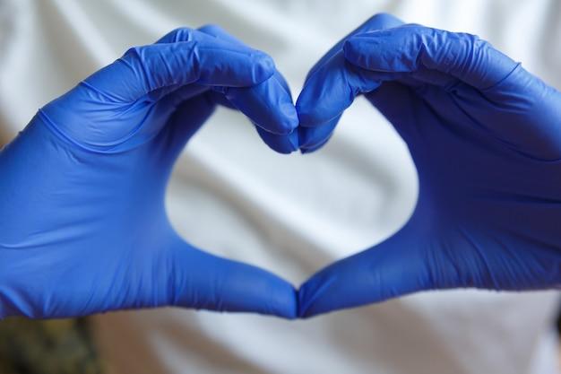 Hände in blauen medizinischen handschuhen halten finger in form eines herzens. handgeste.