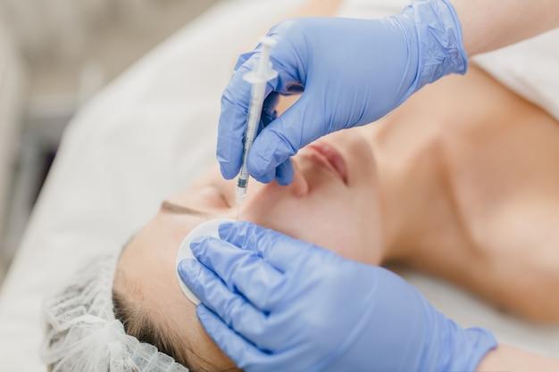Hände in blauen schimmern der kosmetikerin bei der arbeit mit hübscher frau während der injektion auf gesicht. verjüngung, beruf, gesundheitswesen, medizin, medizinische therapie, hautpflege, botox