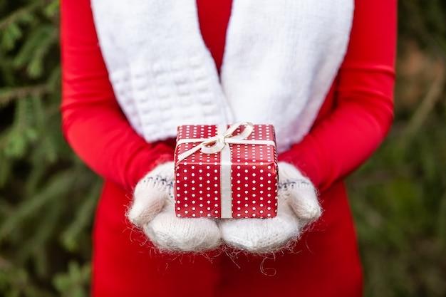Hände in den gestrickten handschuhen, die weihnachtsgeschenkbox halten