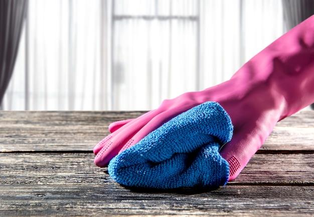 Hände in den gummihandschuhen, die staub auf tabelle mit mikrofasertuch abwischen