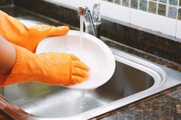 Hände in den gummihandschuhen, die teller mit löffel waschen