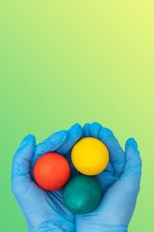 Hände in den medizinischen schutzhandschuhen, die bunte ostereier auf einem gelbgrünen hintergrund des gradientenfrühlings halten