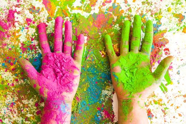 Hände in den rosafarbenen und grünen farben auf hellen trockenen farben