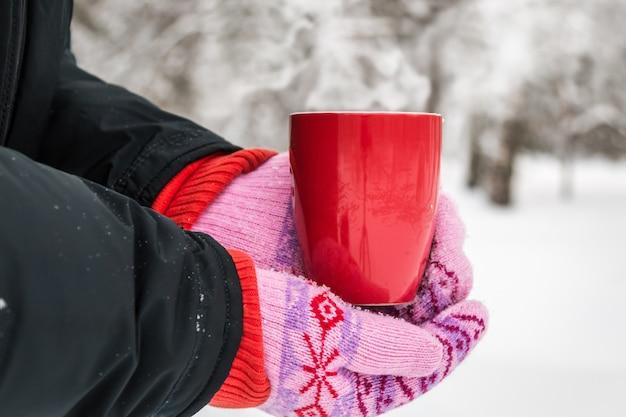 Hände in den weihnachtshandschuhen, die einen becher des heißen getränks im park halten