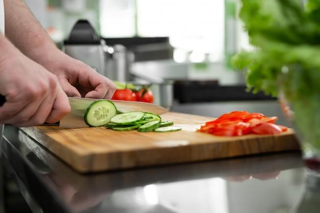 Hände in der küche schneiden frisches gemüse für einen salat
