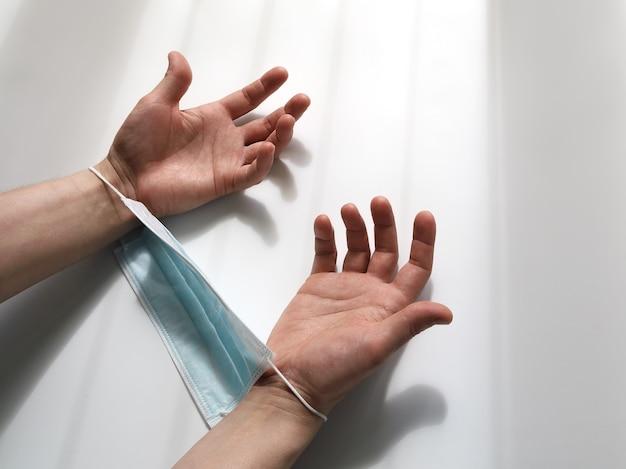 Hände in eine medizinische maske gefesselt und verzweifelt gesenkt