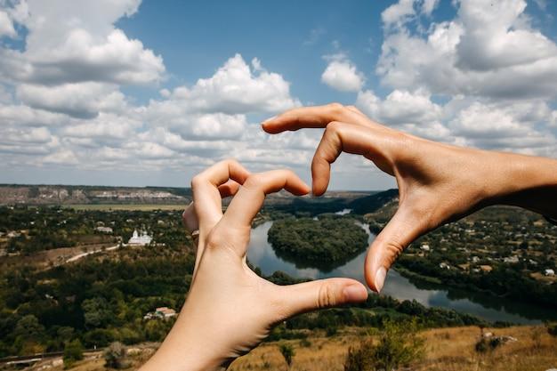Hände in form eines herzens mit blick auf den fluss drienster, moldawien.