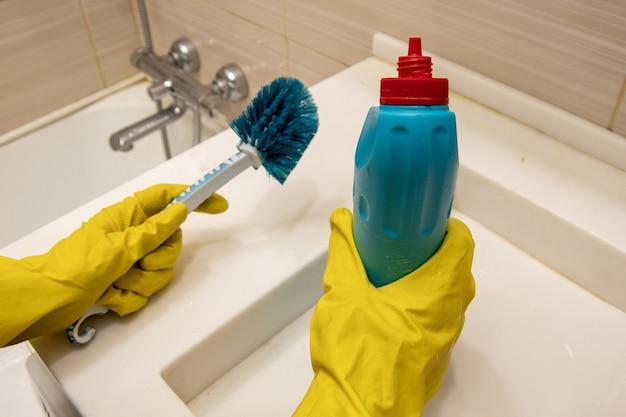Hände in gelben handschuhen halten reinigungsmittel und blauen schwamm am griff zum reinigen des badezimmers. das konzept der hausaufgaben, desinfektion