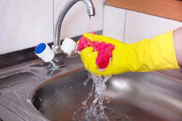 Hände in gelben handschuhen reinigen das waschbecken mit einem schwamm und einem speziellen reinigungsmittel, waschmittelspray. hygiene in der küche, reinigung der küche, haushalt. hand drückt schwamm und sprüht wassertropfen.