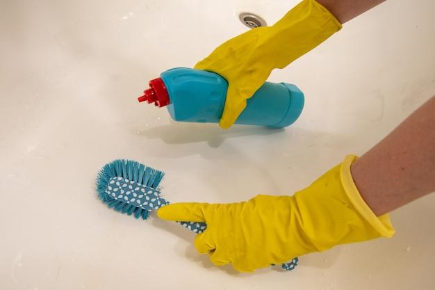 Hände in gelben handschuhen reinigt das weiße bad mit einem reinigungsmittel und einem blauen schwamm am griff. das konzept der desinfektion