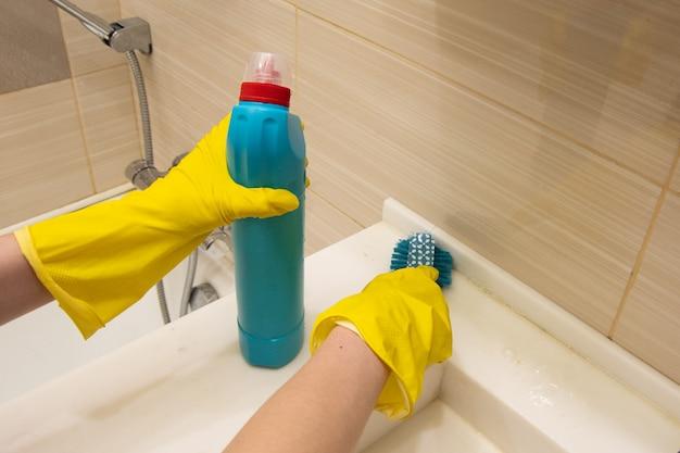 Hände in gelben handschuhen reinigt das weiße bad mit einem reinigungsmittel und einem blauen schwamm am griff. das konzept der hausaufgaben, desinfektion
