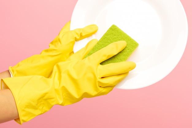 Hände in gelben schutzhandschuhen, die einen teller waschen