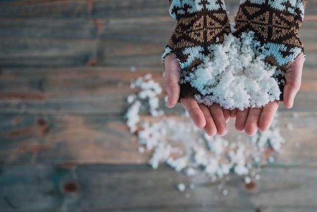 Hände in gestrickte handschuhe mit schnee