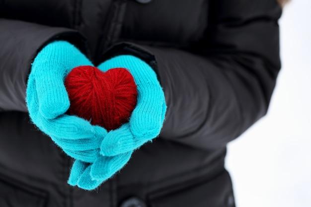 Hände in gestrickten handschuhen, die rotes herz halten