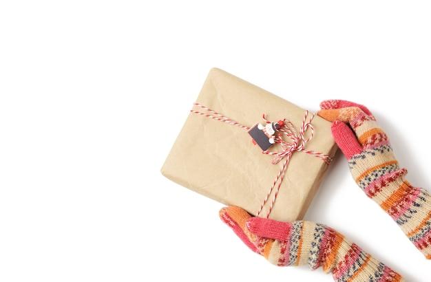 Hände in gestrickten handschuhen halten eine schachtel, die in braunes papier gewickelt und mit einem seil auf einer weißen oberfläche gebunden ist, draufsicht