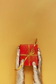 Hände in goldenen medizinischen handschuhen, die weihnachtsrote geschenkbox mit goldener schleife auf goldhintergrund halten.