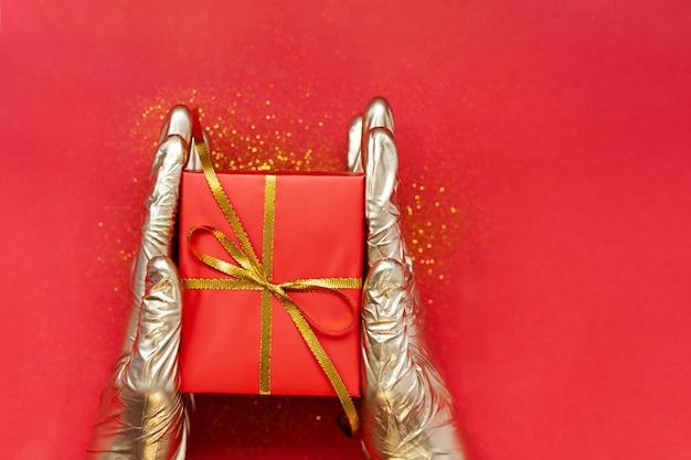 Hände in goldenen medizinischen handschuhen, die weihnachtsrote geschenkbox mit goldener schleife auf rotem hintergrund halten. weihnachts- und neujahrskonzept des sicherheitsgeschenks.