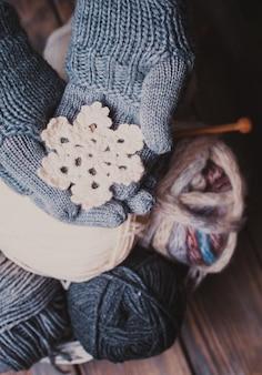 Hände in grauen handschuhen, die weiße gestrickte schneeflocke als wintersymbol halten