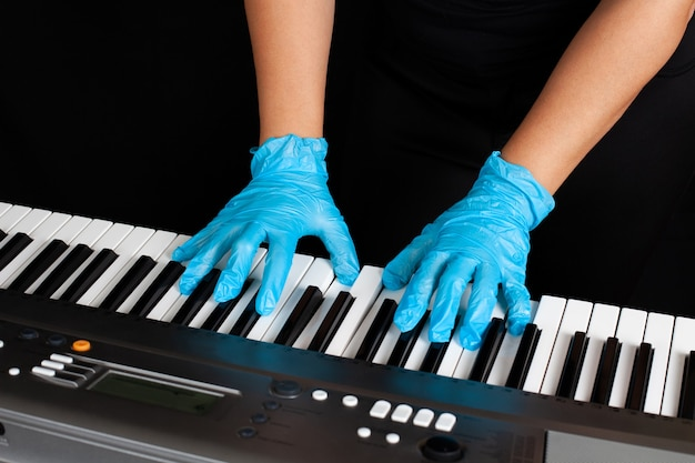 Hände in gummihandschuhen beim klavierspielen, schutz vor bakterien bei konzerten