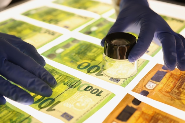 Hände in gummihandschuhen, die lupe über banknoten-nahaufnahme halten. geldauthentifizierungskonzept
