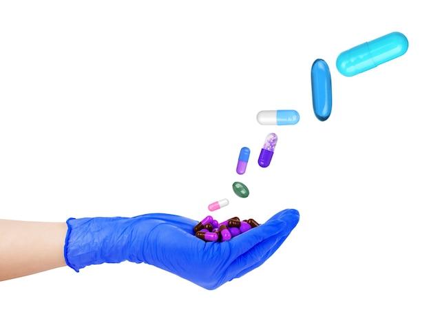 Hände in gummihandschuhen, die pillen auf weißem hintergrund halten